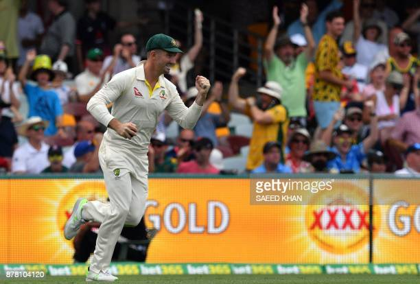 Australia's Shaun Marsh celebrates after taking a successful catch of England's batsman Dawid Malan on the second day of the first cricket Ashes Test...