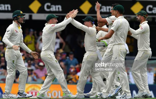 Australia's Shaun Marsh celebrates with teammates after taking a successful catch to dismiss England's batsman Dawid Malan on the second day of the...