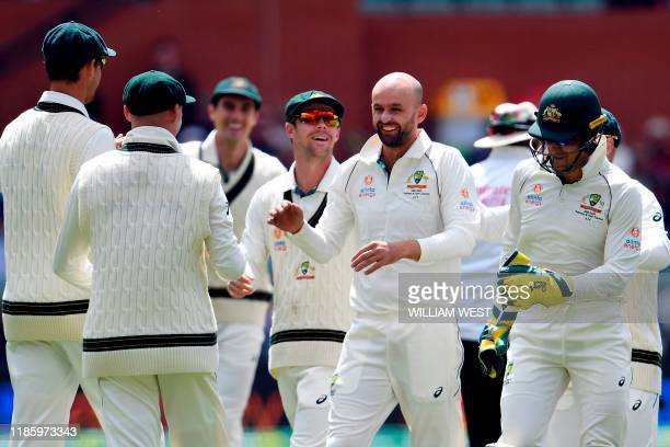 Australia's spin bowler Nathan Lyon celebrates his wicket of Pakistan's batsman Shan Masood with teammates during the day four of the second cricket...