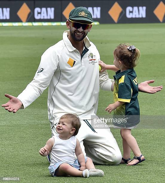 Australia's spin bowler Nathan Lyon plays with his daughter Harper and a teammate David Warner's daughter Ivy following team's victory over New...