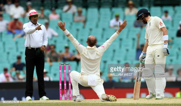 Australia's spinner Nathan Lyon appeals successfully against England batsman Moeen Ali as Jonny Bairstow reacts on the final day of the fifth Ashes...