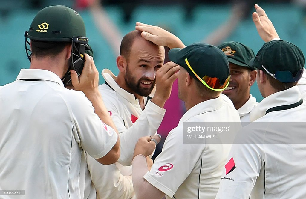Australia's spinner Nathan Lyon (C) is patted on the head after dismissing Pakistan batsman Wahab Riaz during the third day of the third cricket Test match at the SCG in Sydney on January 5, 2017. / AFP / WILLIAM