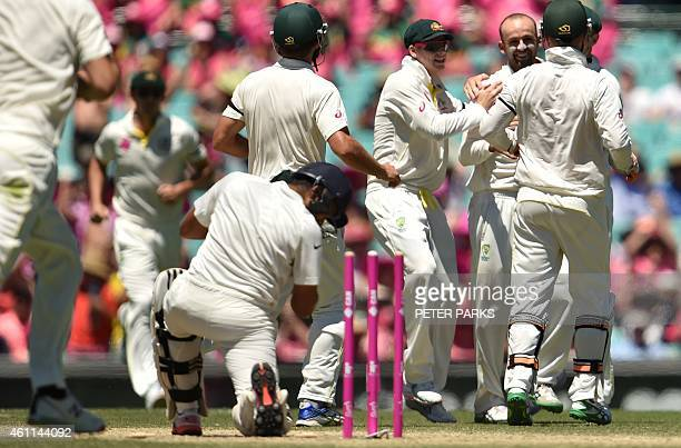 Australia's spinner Nathan Lyons is congratulated by teammates after bowling out India's batsman Karn Sharma during day three of the fourth cricket...
