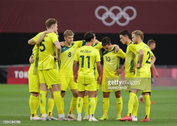 Australia's starting players gather on the pitch prior to their Tokyo 2020 Olympic Games men's group C first round football match between Australia...