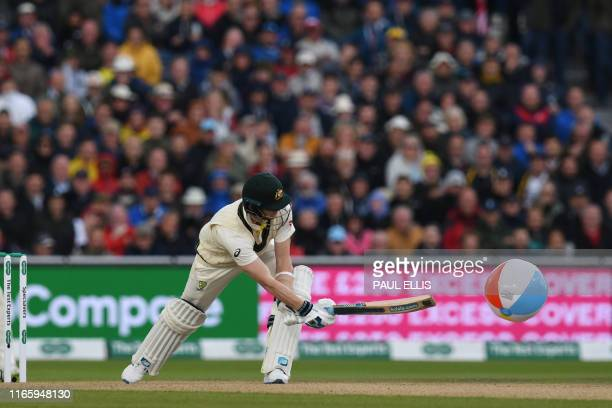 Australia's Steve Smith bats a beach ball which landed on the pitch on the first day of the fourth Ashes cricket Test match between England and...