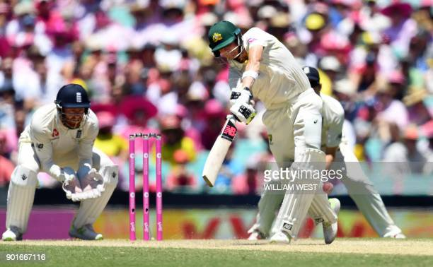 Australia's Steve Smith hits a return catch to the bowler as England wicketkeeper Jonny Bairstow looks on on the third day of the fifth Ashes cricket...