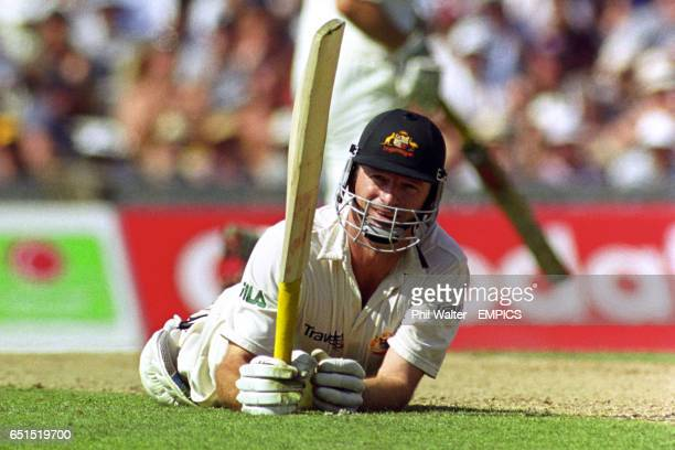 Australia's Steve Waugh acknowledges his century as he lies on the pitch after a near runout.