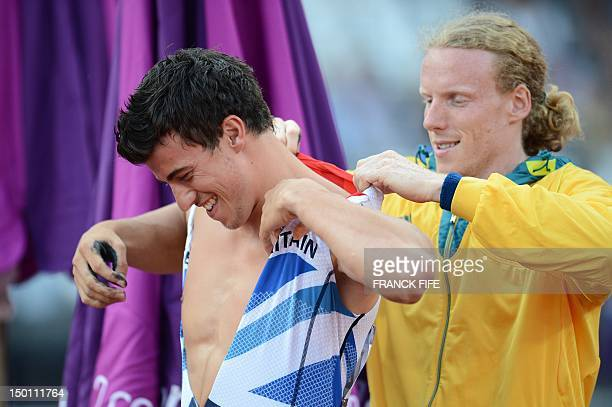 Australia's Steven Hooker helps Britain's Steven Lewis to adjust his vest by prior to competing in the men's pole vault final at the athletics event...