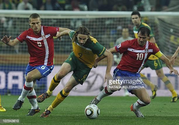 Australia's striker Josh Kennedy is challenged for the ball by Serbia's defender Nemanja Vidic and Serbia's midfielder Dejan Stankovic during the...