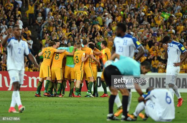 Australia's team celebrates their victory, as Honduras' players react, after their World Cup 2018 qualifying football match in Sydney on November 15,...