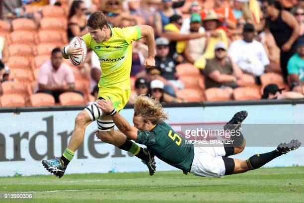 Australia's Tim Anstee runs away for a try despite the tackle from South Africa's Werner Kok during the World Rugby Sevens Series semi final match...