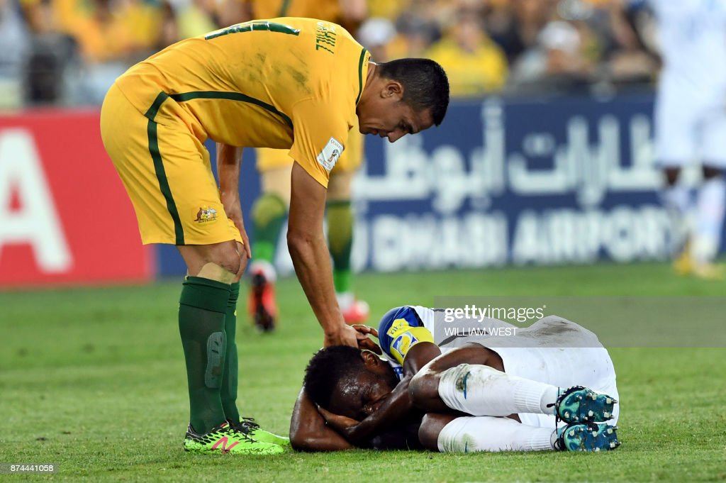 Australia's Tim Cahill (L) attempts to help Honduras' Maynor Figueroa to his feet after Australia defeated Honduras in their 2018 World Cup qualification play-off football match at Stadium Australia in Sydney on November 15, 2017. / AFP PHOTO / William WEST / -- IMAGE
