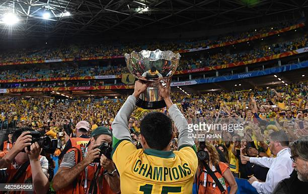 Australia's Tim Cahill lifts the AFC Asian Cup football trophy after beating South Korea at Stadium Australia in Sydney on January 31 2015 AFP PHOTO...