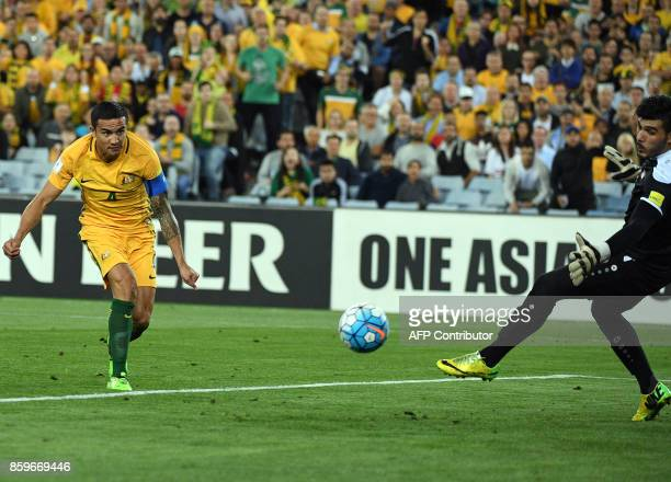 Australia's Tim Cahill watches his header for a successful goal as Syria's goakeeper Ibrahim Alma fails to block during their 2018 World Cup football...