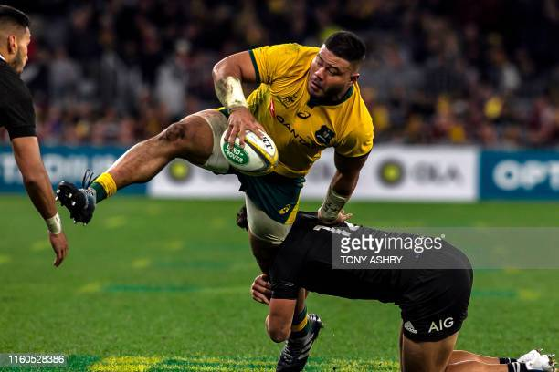 TOPSHOT Australias Tolu Latu is tackled by New Zealand's Anton LienertBrown during the Rugby Championship Bledisloe Cup Test match between the...