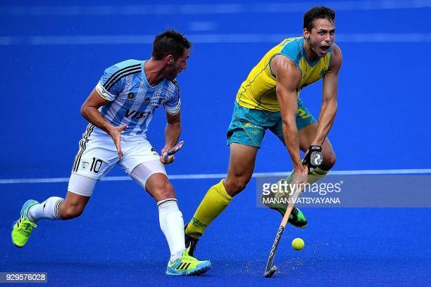 Australia's Tom Craig vies for the ball with Matias Paredes of Argentina during their men's field hockey match of the 2018 Sultan Azlan Shah...