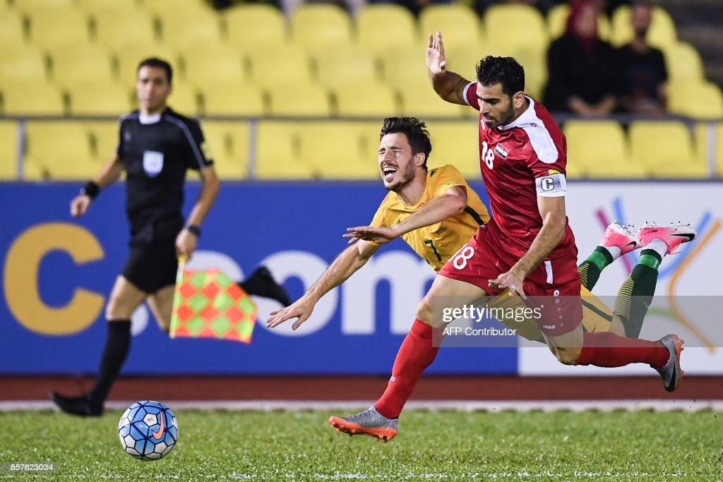 Australia's Tomi Juric (L) and Syria's Zaher Almedani (R) compete for the ball during the 2018 World Cup qualifying football match between Syria and Australia at the Hang Jebat Stadium in Malacca on October 5, 2017. /