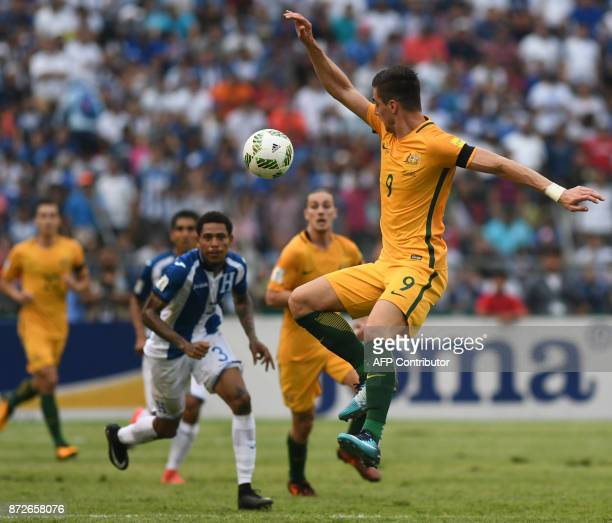 Australia's Tomi Juric jump for the ball during the first leg football match of their 2018 World Cup qualifying playoff against Honduras in San Pedro...