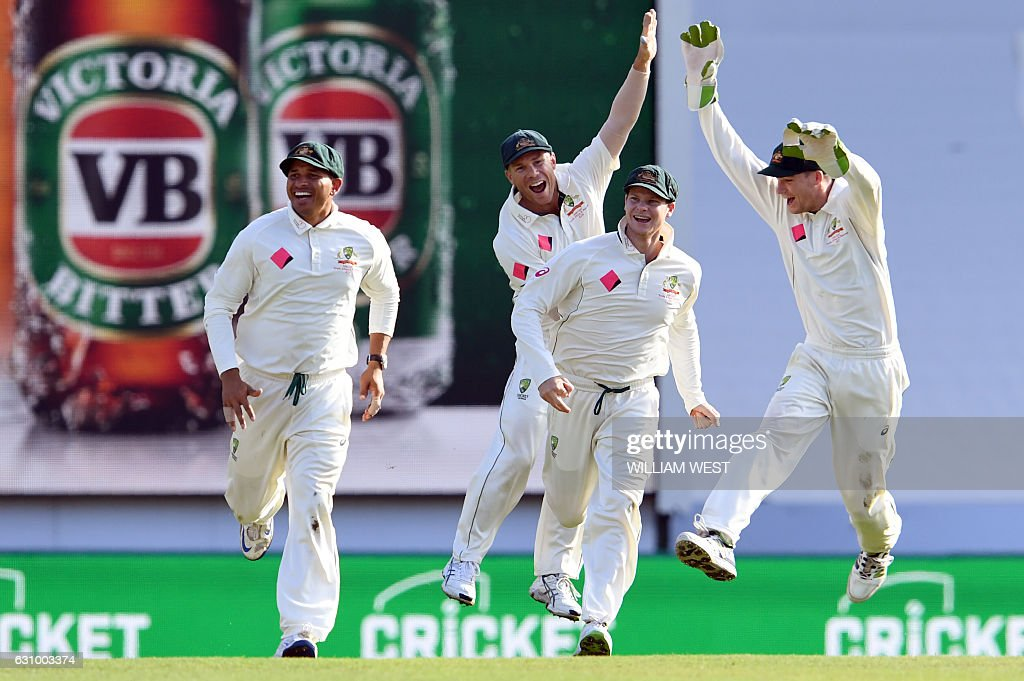 Australia's Usman Khawaja (L), David Warner (2nd L), Steve Smith (2nd R) and Peter Handscomb (R) celebrate after the dismissal of Pakistan batsman Sarfraz Ahmed during the third day of the third cricket Test match at the SCG in Sydney on January 5, 2017. / AFP / WILLIAM