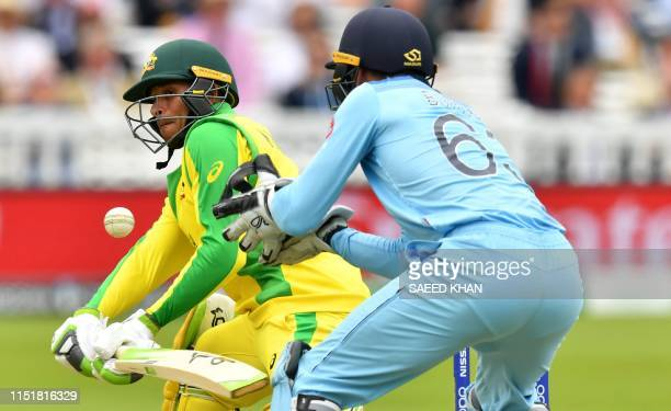Australia's Usman Khawaja plays a shot as England's wicketkeeper Jos Buttler looks on during the 2019 Cricket World Cup group stage match between...