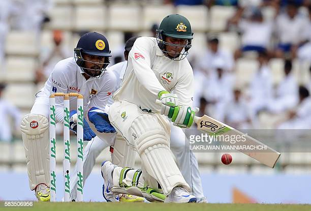 Australia's Usman Khawaja plays a shot as Sri Lanka's wicketkeeper Dinesh Chandimal looks on during the first day of the opening Test cricket match...