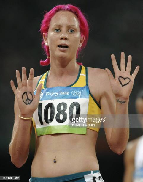 Australia's Victoria Mitchell shows her palms bearing a heart and a peace sign after competing in the women's first round 3000m steeplechase heat 1...
