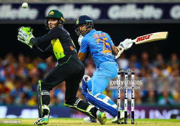 Australia's wicketkeeper Alex Carey misses a catch in front of India's Shikhar Dhawan during the T20 international cricket match between Australia...