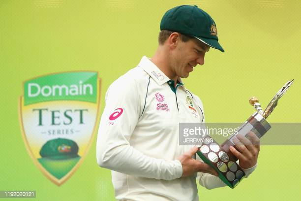Australias wicketkeeper and captain Tim Paine looks at the TransTasman Trophy after winning the third cricket Test match and series between Australia...