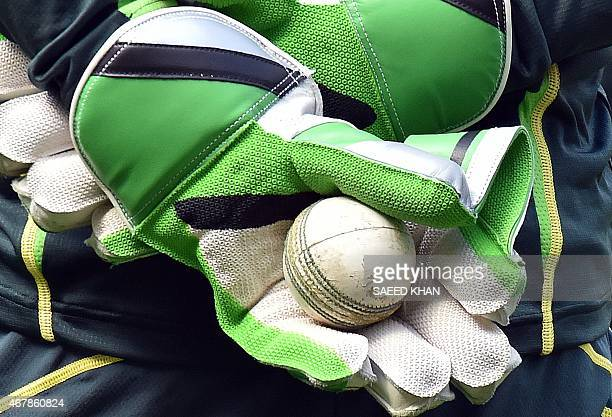 Australia's wicketkeeper Brad Haddin holds a ball in his gloves during a practice session ahead of the 2015 Cricket World Cup final between Australia...