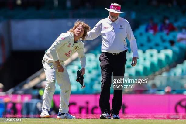 Australia's Will Pucovski reacts after being hurt while fielding as umpire Paul Wilson watches during the fifth day of the third cricket Test match...
