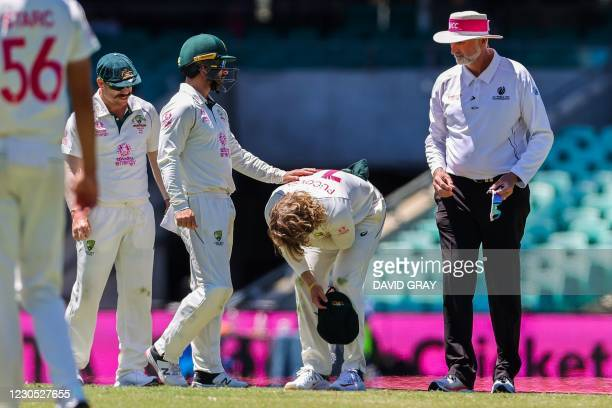 Australia's Will Pucovski reacts after being hurt while fielding during the fifth day of the third cricket Test match between Australia and India at...