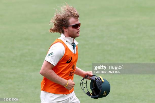 Australia's Will Pucovski runs a helmet for a fielder on day three of the fourth cricket Test match between Australia and India at The Gabba in...