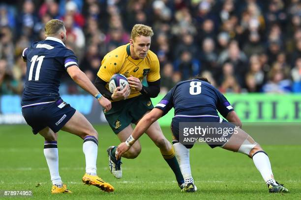 Australia's wing Reece Hodge is tackled by Scotland's wing Byron McGuigan and Scotland's number 8 Ryan Wilson during the autumn international rugby...