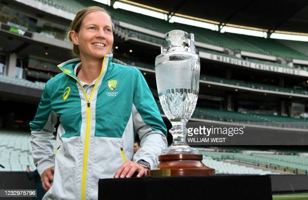 Australia's women's cricket captain Meg Lanning poses with the trophy after the announcement of the upcoming men's and women's Ashes series against...
