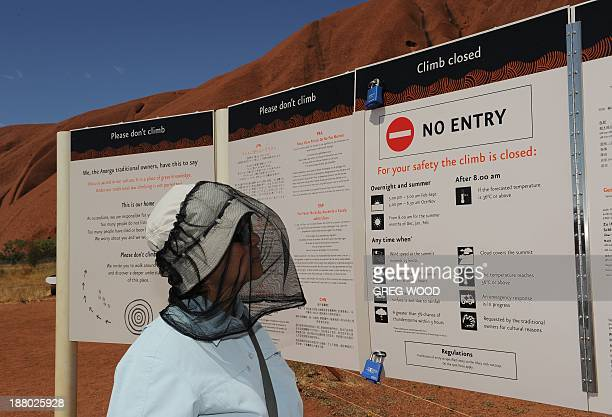 AustraliatourismindigenousUluruFEATURE by Madeleine Coorey This photo taken on October 11 2013 shows a tourist looking at a sign stating that the...