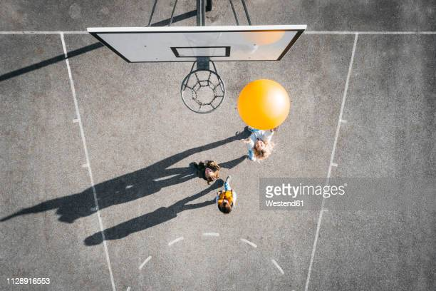 austria, aerial view of basketball field, mother and children playing basketball with big ball - gelb stock-fotos und bilder