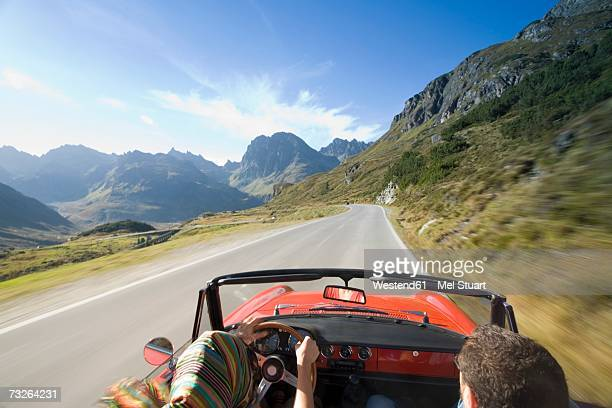 Austria, Alps, Couple driving in convertible car, rear view, (blurred motion)