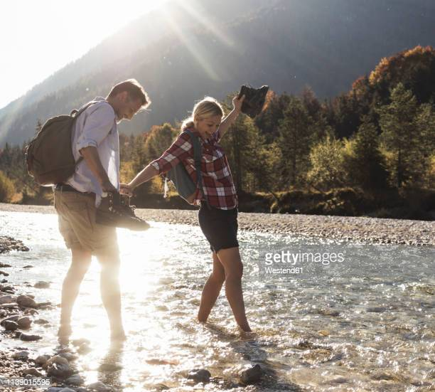 austria, alps, couple on a hiking trip wading in a brook - bach stock-fotos und bilder