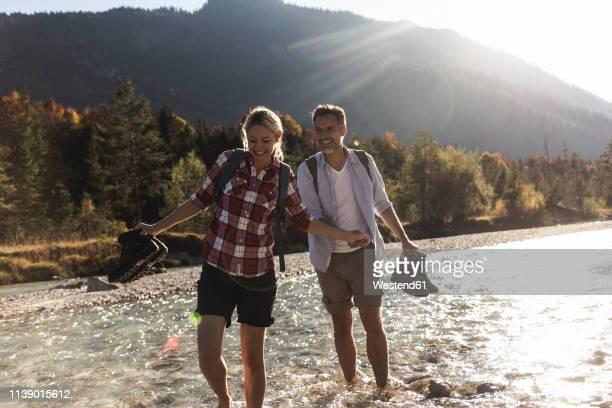 austria, alps, couple on a hiking trip wading in a brook - aktiver lebensstil stock-fotos und bilder