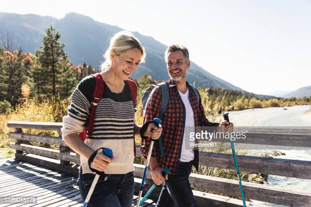 austria, alps, happy couple on a hiking trip crossing a bridge - 40 49 jaar stockfoto's en -beelden