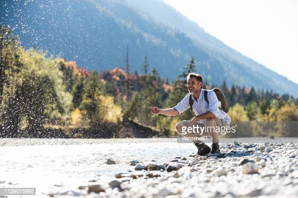 austria, alps, man on a hiking trip having a cooling break at a brook - wasserrand stock-fotos und bilder