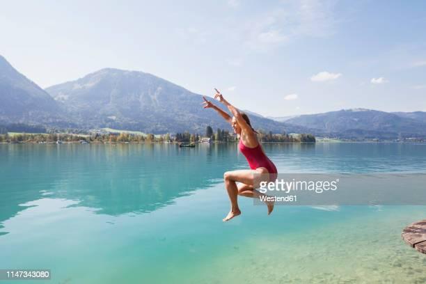 austria, alps, salzburg, salzkammergut, salzburger land, wolfgangsee, woman jumping into lake - see stock-fotos und bilder