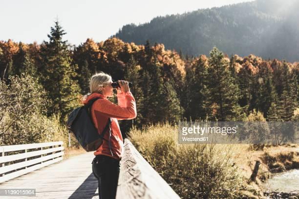 austria, alps, woman on a hiking trip looking through binoculars - vinden stockfoto's en -beelden