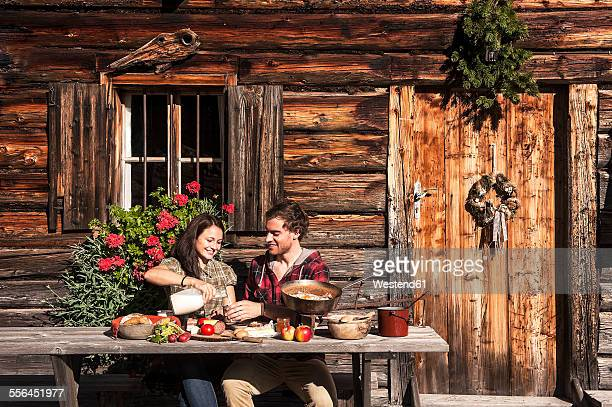 Austria, Altenmarkt-Zauchensee, couple having a break at alpine cabin