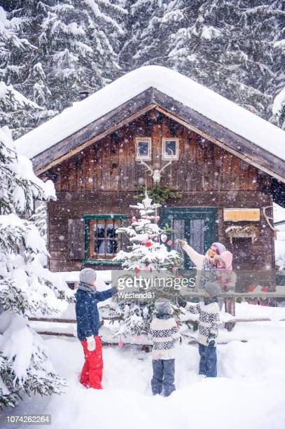 austria, altenmarkt-zauchensee, family decorating christmas tree at wooden house - country christmas bildbanksfoton och bilder