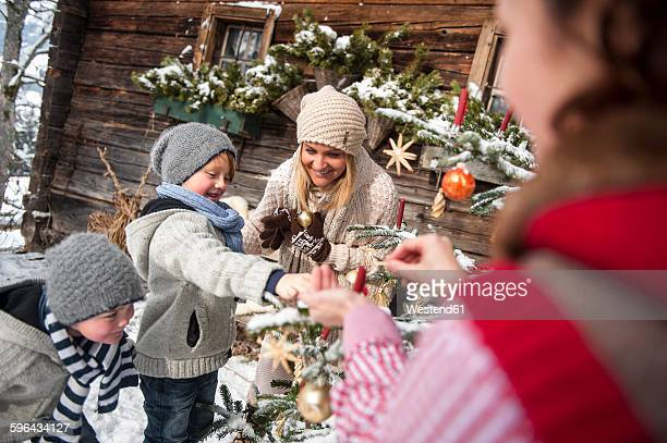 Austria, Altenmarkt-Zauchensee, family decorating Christmas tree in front of farmhouse