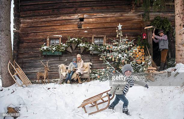 Austria, Altenmarkt-Zauchensee, family in front of farmhouse at Christmas time