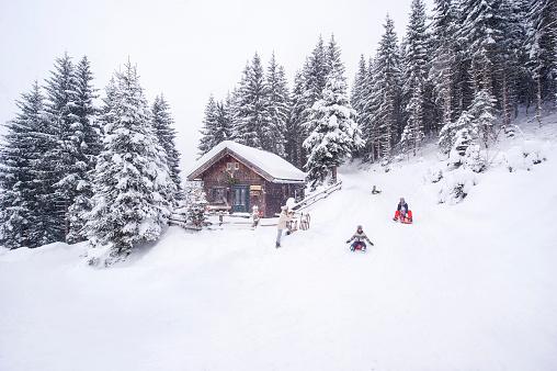 Austria, Altenmarkt-Zauchensee, family tobogganing at wooden house at Christmas time - gettyimageskorea