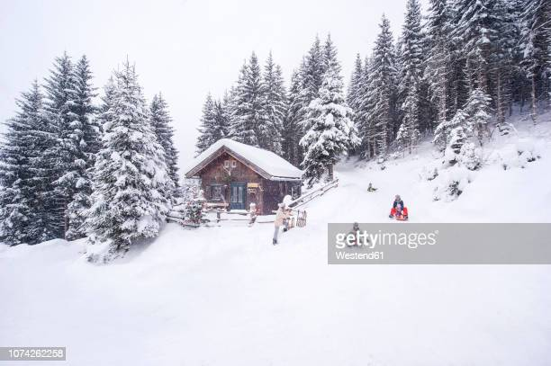 austria, altenmarkt-zauchensee, family tobogganing at wooden house at christmas time - country christmas stock pictures, royalty-free photos & images