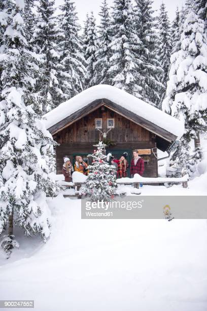 austria, altenmarkt-zauchensee, friends decorating christmas tree at wooden house - cabaña fotografías e imágenes de stock